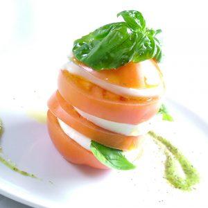 立川駅1分 本格パスタが美味しいイタリアン&スパニッシュのお店『CANTINA 立川店』でいただける、輪切りのトマトとモッツアレラチーズがミルフィーユのように交互に重ねられ、その上にバジルの葉が乗った料理