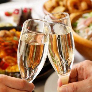 立川駅1分 本格パスタが美味しいイタリアン&スパニッシュのお店『CANTINA 立川店』にて、2人の人間が白のスパークリングワインが入ったグラスで乾杯しているところ