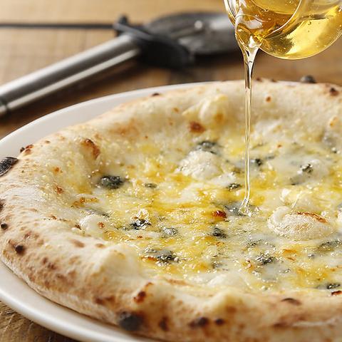 立川駅1分、本格パスタが美味しいイタリアン&スパニッシュのお店『CANTINA 立川店』のおすすめメニューの1つ、チーズの塩気と蜂蜜の甘みが美味しいピザ〈クアトロフォルマッジ〉にハチミツがかけられている画像