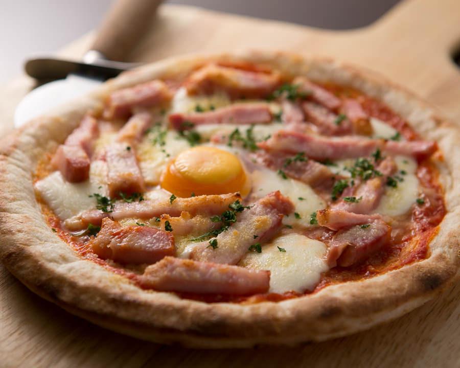 立川駅1分、本格パスタが美味しいイタリアン&スパニッシュのお店『CANTINA 立川店』で堪能できる、半熟卵ととろ~りチーズが相性抜群のピザ(ピッツァ)〈ビスマルク〉が木製プレートの上に乗っている画像